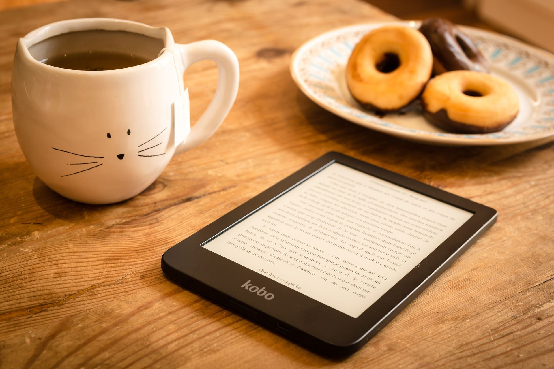 E-reader with tea and donut
